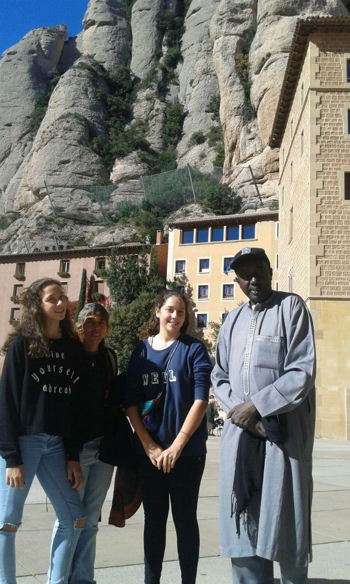 Profesor Sene (derecha) en el Monasterio de Montserrat, acompañado de voluntarias de la FYME.