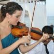 Es nuestra hija y su violín (comprado por sus padres) tocando en la celebración de una boda familiar a la orilla de una playa del Mar Mediterráneo.