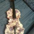 Violín decorado con pétalos de flores sobre fondo tapizado. Juan José Carretero Fernández.